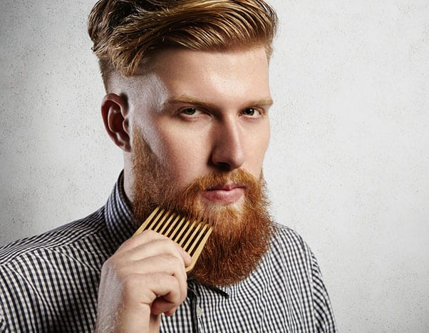 Portrait of young attractive redhead hipster male with serious and confident look, holding wooden comb and doing his thick beard. Stylish bearded barber in checkered shirt combing in salon. Horizontal