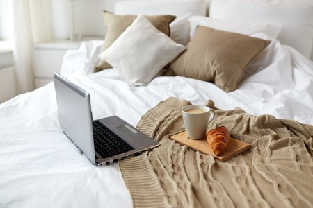 68094645 - coziness, technology, interior and winter concept - cozy bedroom with laptop computer, coffee cup and croissant on bed at home