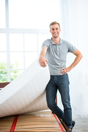 49654401 - photo of young man standing near nice white bed. young man demonstrating quality of mattress
