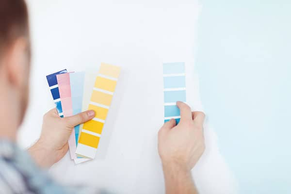 2 man choosing paint color - DIY vs. Tradesman Hire: A few easy home repairs every man should master