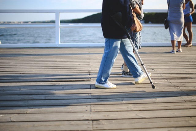 woman walking jeans pier - Steps You Should Take After Being Injured