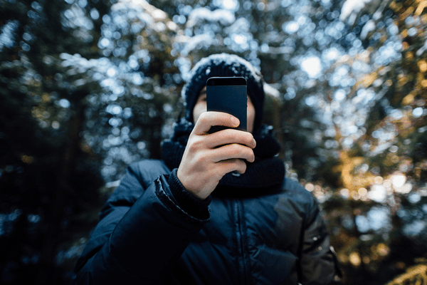 A young man using his smartphone in the snow.