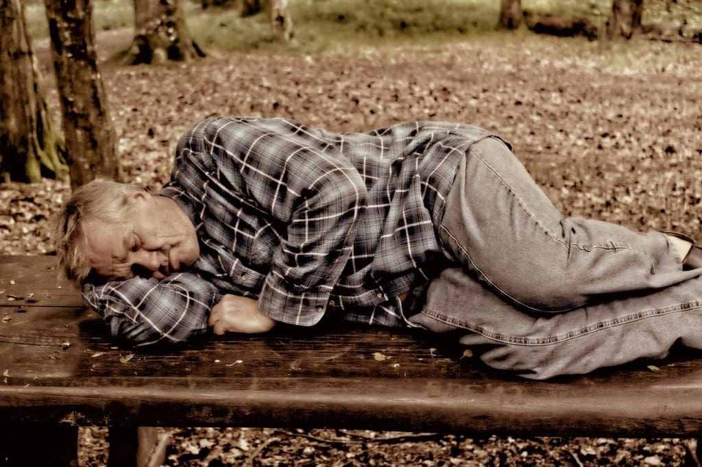 man sleepin in park 1024x682 - Living In The City Vs. Living In The Suburbs: Pros And Cons