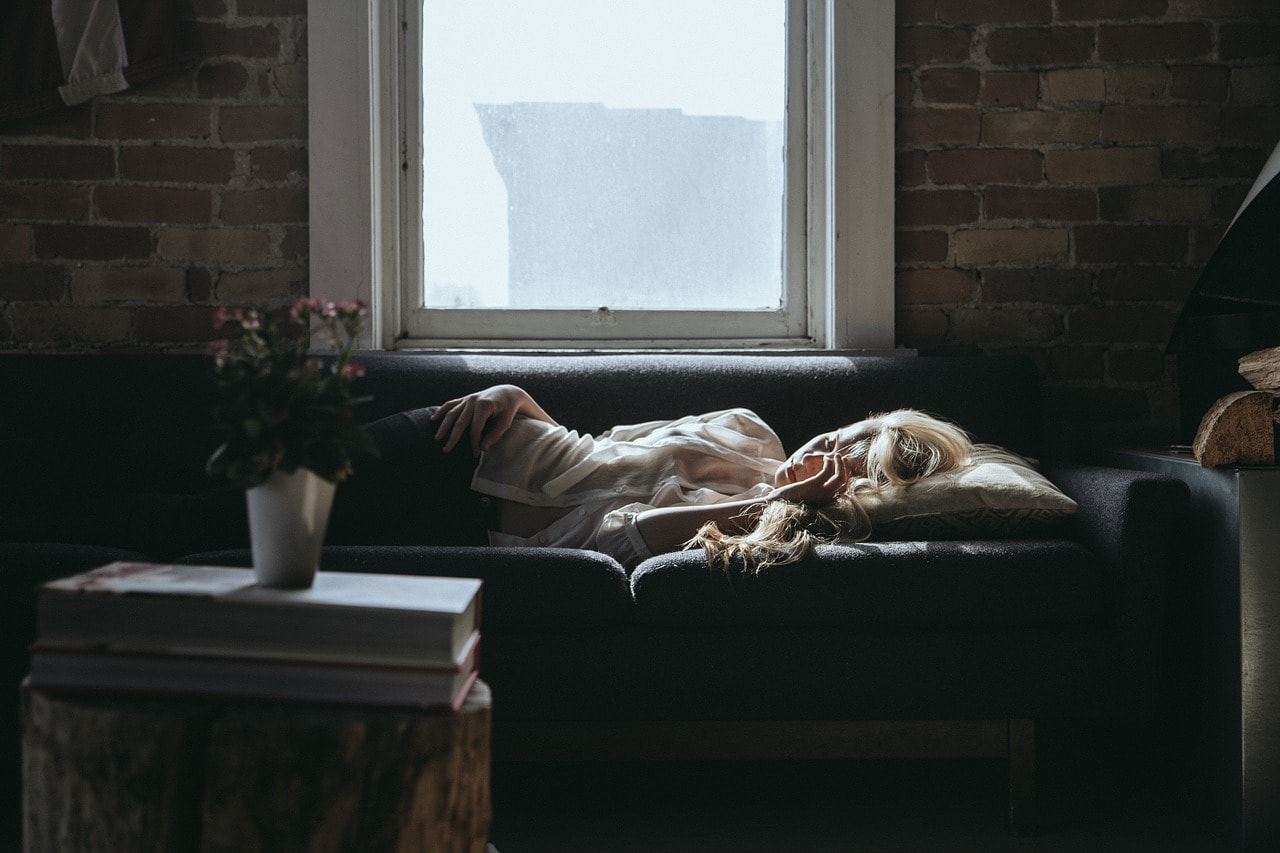 woman sleeping on a sofa - Learn How to Sleep on Your Side for Better Health