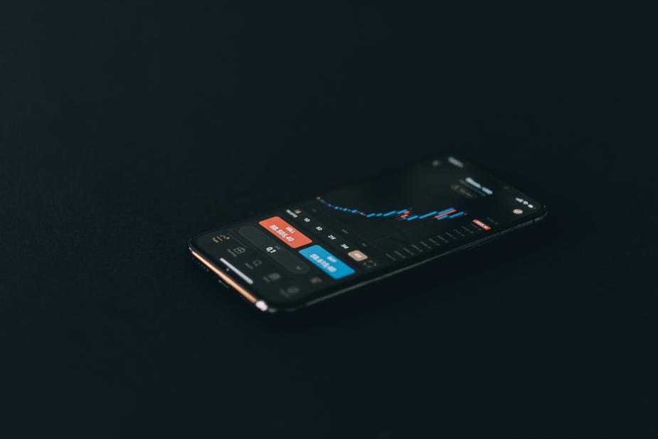 cell phone laying on a black surface displaying a graph - CFDs and Exchange in Cryptocurrency Trading