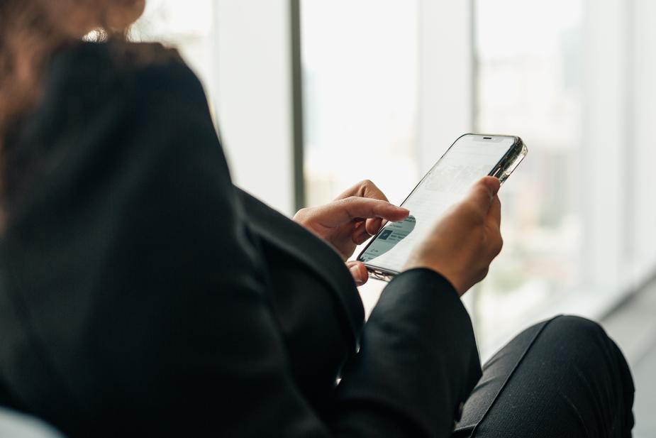 woman holding phone browsing social media - Estate Agent Marketing Ideas